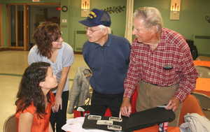 Collinsville High School students Morgan Manning (seated) and Kristen Dugger listen to World War II veterans Mel Lindauer, of Belleville, and Ed Fiedler, of Swansea, who shared their old photos with students for their Illinois WWII Classroom Projects. The school's World History and Video Production classes participated in the project by videotaping interviews with veterans to produce a digital video storybook. - Provided/BND